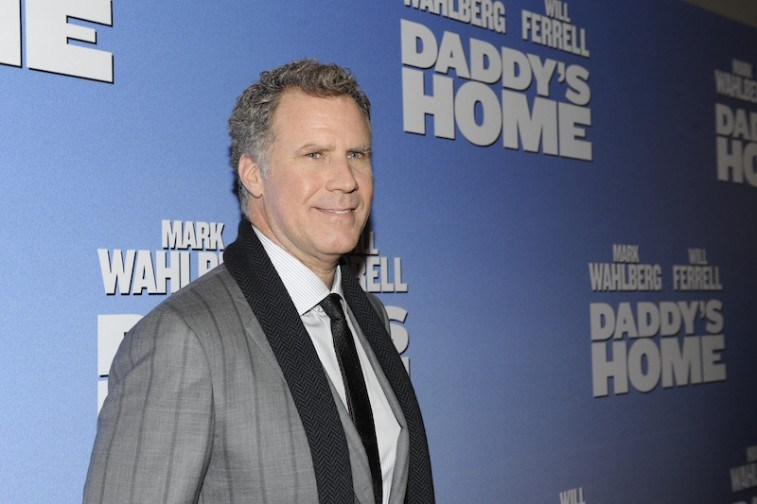 Will Ferrell smiling on the red carpet in a grey suit