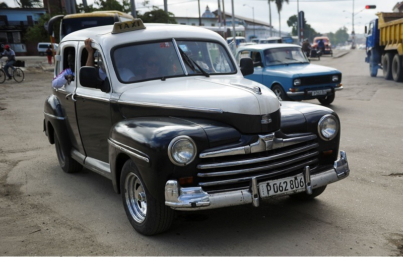 TO GO WITH AFP STORY by Rigoberto Diaz People drive cars along the streets of Havana, on January 11, 2016. A third of the cars riding in Cuba do so with mechanical failures and on destroyed roads.
