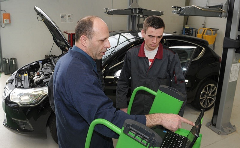 An apprentice mechanic works on a car with his trainer (L) at the Apprentice Training Center (CFA) of the Campus des Metiers (Job Campus) in Quimper, western France, on February 24, 2016.