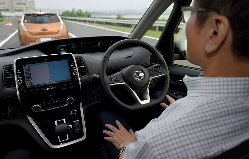 A journalist sitting in the driver's seat of the all-new minivan Serena from Japanese auto giant Nissan Motor takes his hands off the steering wheel during a test drive, at the test course of the company's Oppama plant in Yokohsuka, in suburban Tokyo, on July 13, 2016. Nissan will release the new vehicle, equipped with autonomous drive technology designed for highway use in single-lane traffic, in late August.