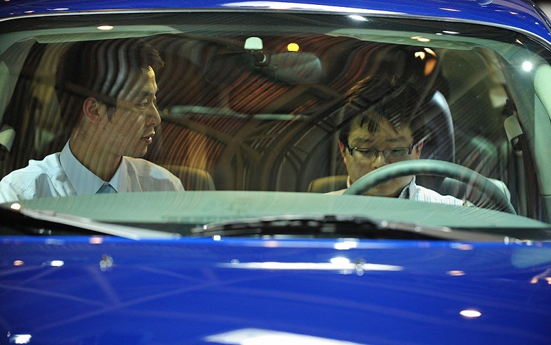 A salesman looks at a potential buyer sitting behind the wheel of a Chrysler PT Cruiser