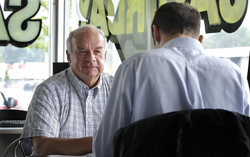 A man prepares to make a deal with a Ford car salesman