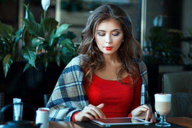Woman works on her tablet in a coffee shop