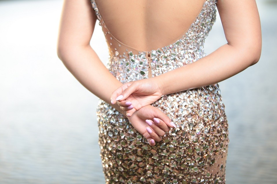 woman wearing sequence dress and pink nail polish