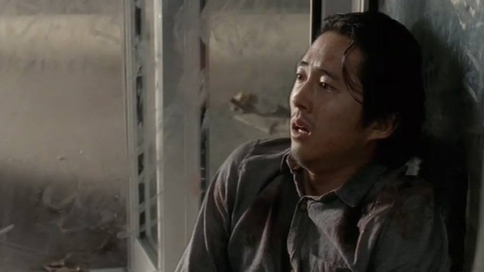Glenn sits against a wall