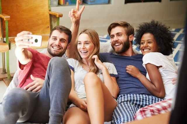 Group of friends takes a selfie on the couch