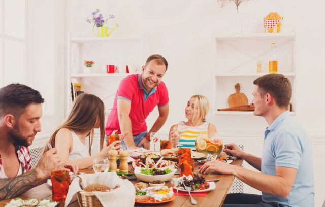 people laugh and chat at dinner table