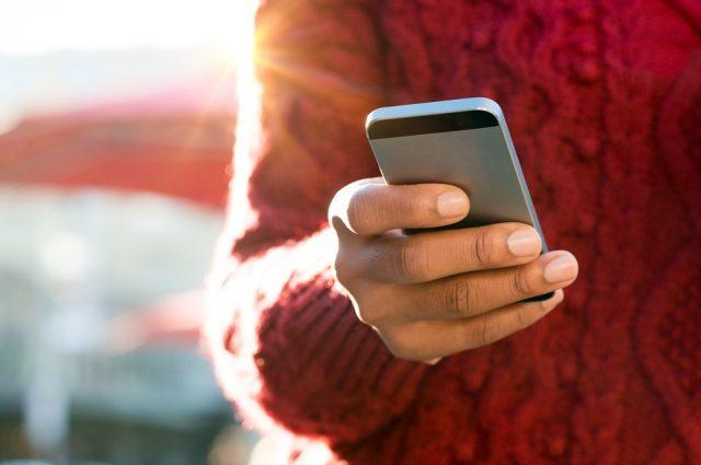 young woman's hand typing text message on her smartphone
