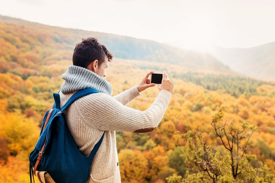 young man taking photograph in autumn