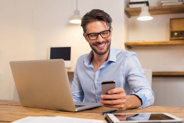 Happy businessman smiling while reading his smartphone.