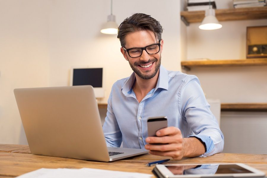 happy businessman smiling while reading his smartphone