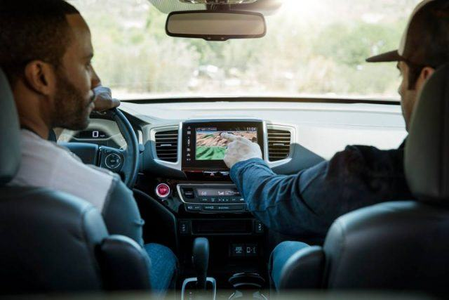 A man shows the inner workings of a Honda touchscreen infotainment display in the all-new Ridgeline