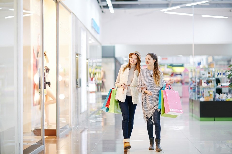 women with paper bags walk inside a mall