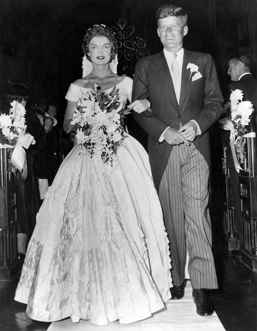 Senator John Fitzgerald Kennedy escorts his bride Jacqueline Lee Bouvier