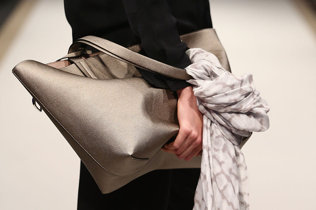 A bag is pictured as a model walks the runway