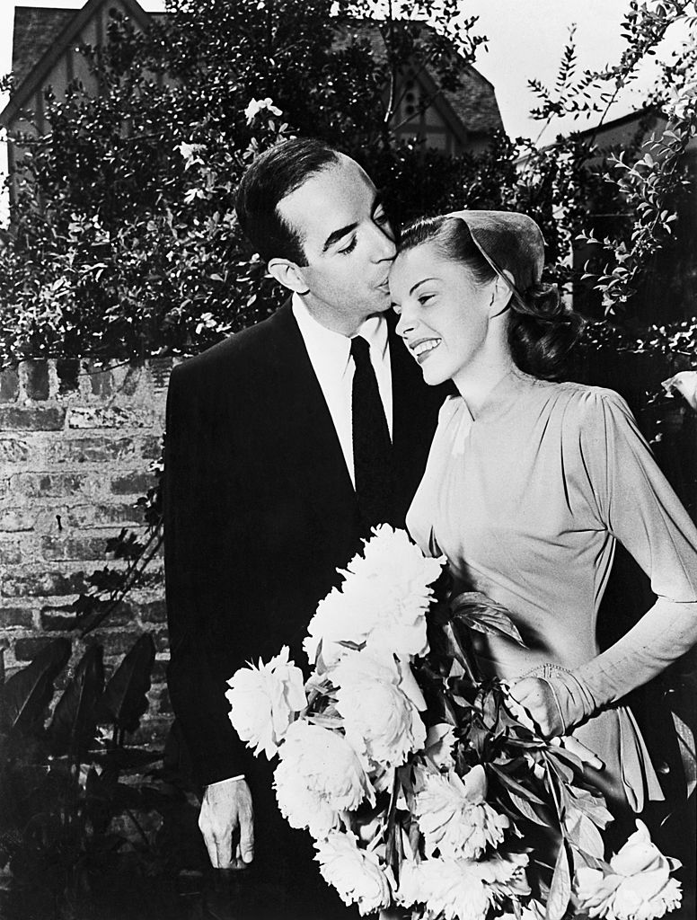 Film director Vincente Minnelli (1903 - 1986) kisses singer and actress Judy Garland