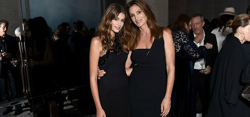 Kaia Gerber and Cindy Crawford pose next to each other in black dresses.