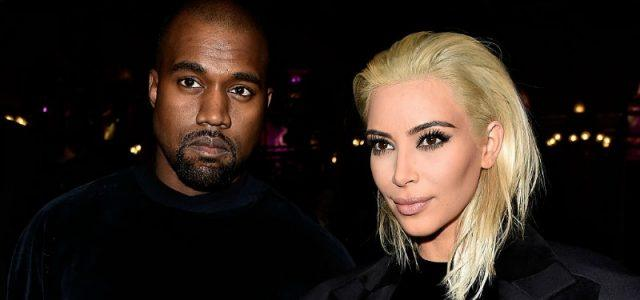 Kim Kardashian and Kanye West standing next to each other while wearing black outfits at a fashion event.