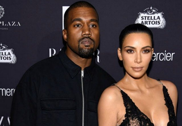 Kanye West and Kim Kardashian stand on a red carpet together.