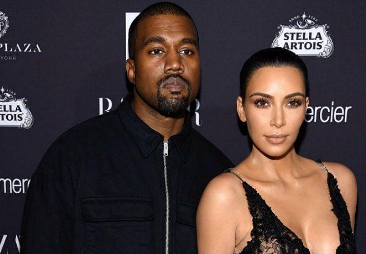 Kanye West stands next to Kim Kardashian