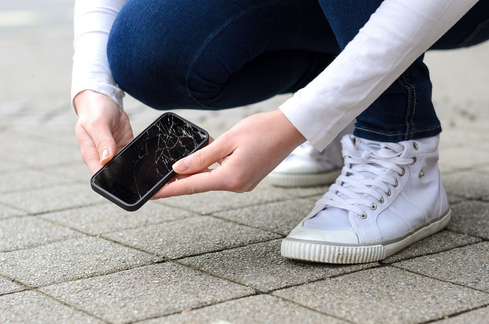 kneeling person in jeans and shoes picking up a broken phone