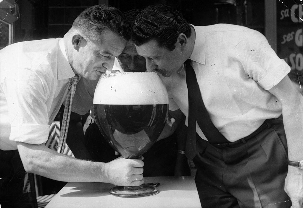 Three men drinking from a large glass of beer