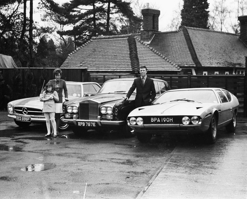 Portrait of millionaire song writer Les Reed and his three luxury cars