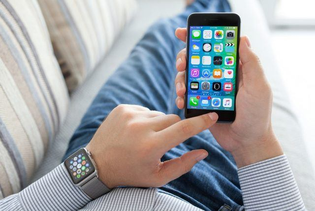 Man hand with Apple Watch holding iPhone