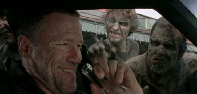 Merle Dixon drinking a glass of bear in his car and two men stare at him through his car.
