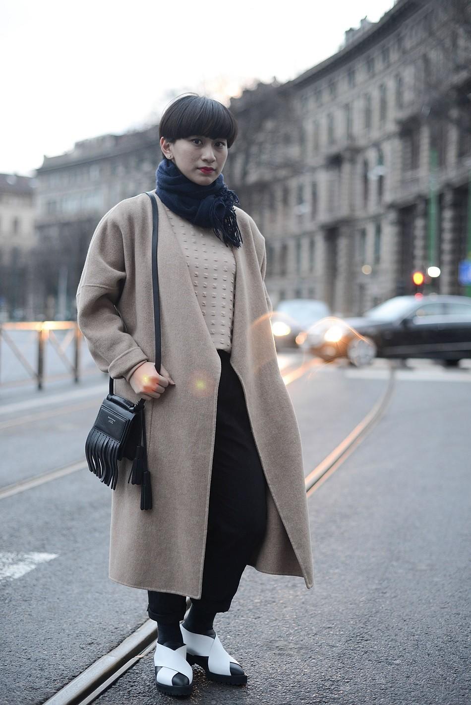 Ayu Ananto poses wearing a Max Mara coat, COS pants, Proenza Schouler shoes and Acne bag