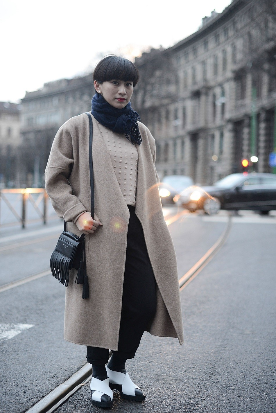 Ayu Ananto poses wearing a Max Mara coat, COS pants, Proenza Schouler shoes and Acne bag