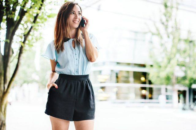 Young woman in trendy clothes talks on a smart phone.