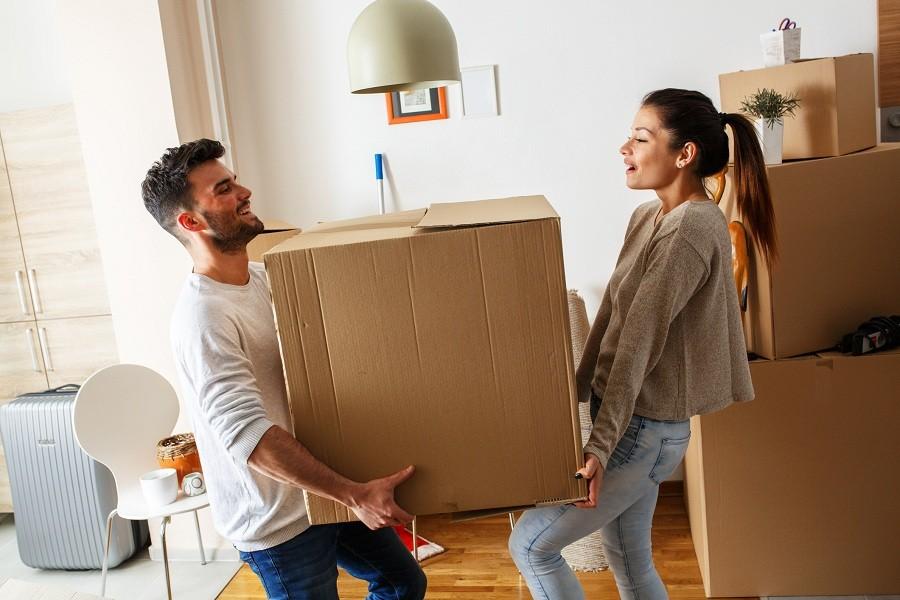 couple carrying big cardboard box