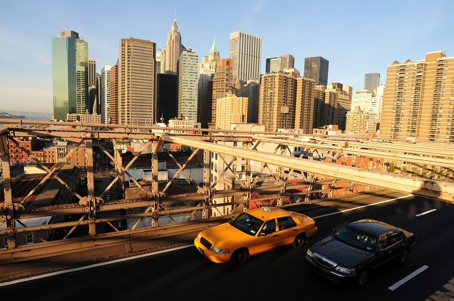 Taxi and a Limousine driving along the Brooklyn bridge