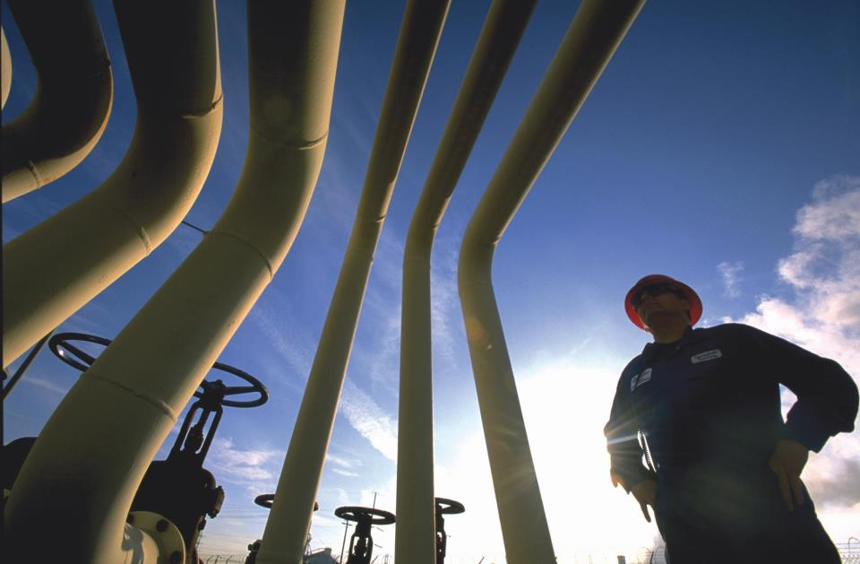 A pipeline worker inspects piping