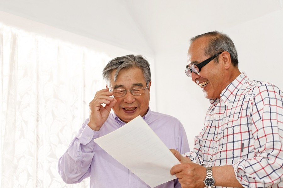 Two men laughing at a piece of paper