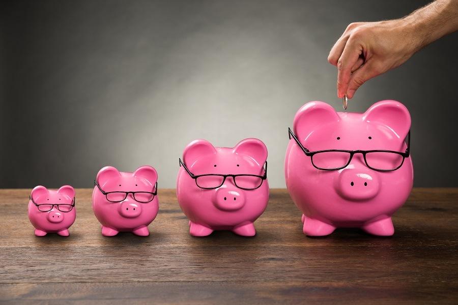 Hand placing coin into a piggy bank