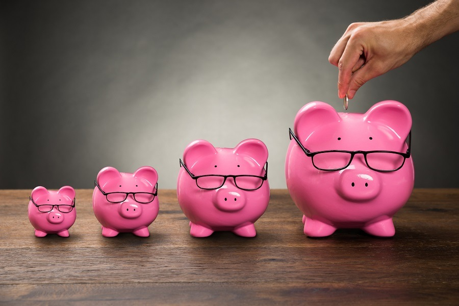 Hand inserting coin into piggy bank next to three smaller piggy banks