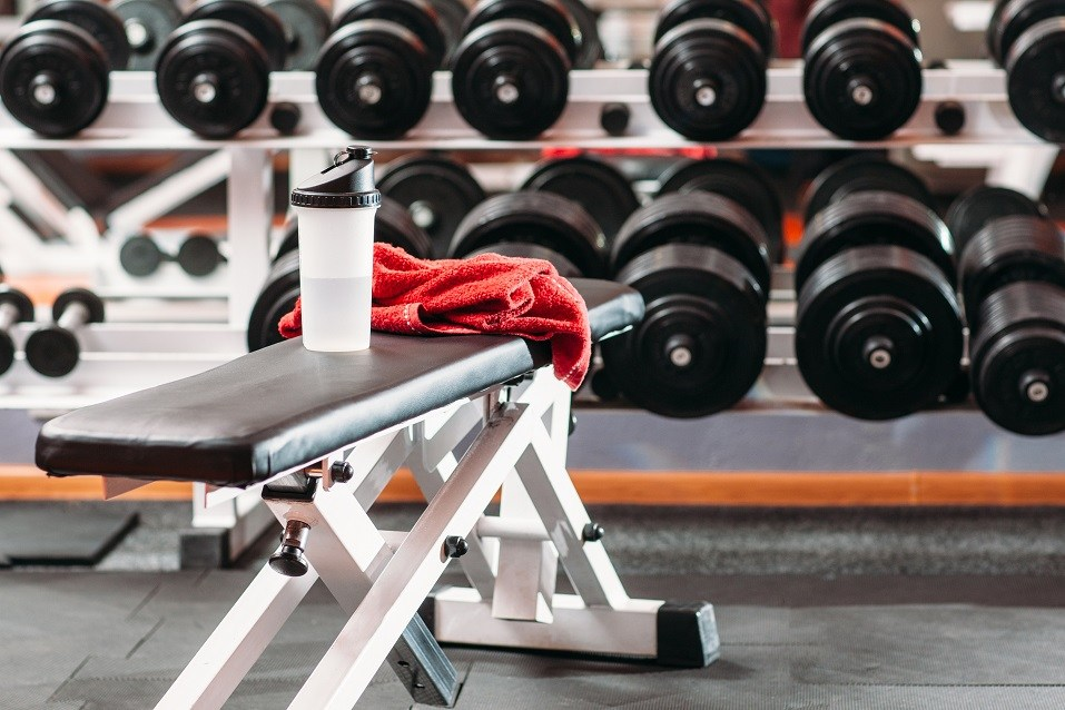 Set of personal sport stuff lay on training bench in fitness gym