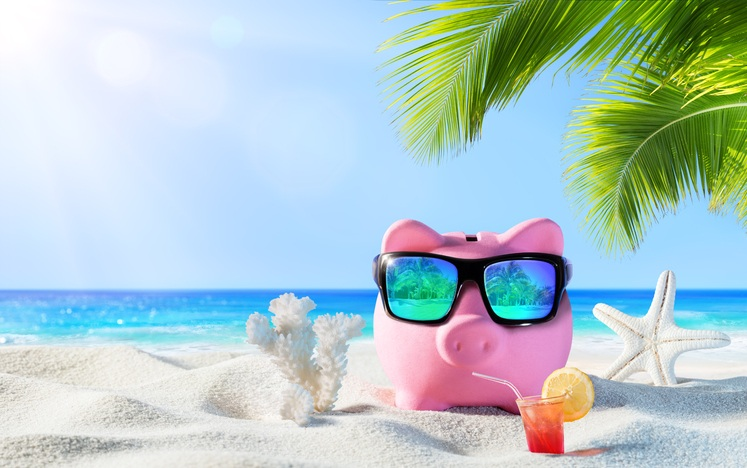 piggy bank drinking cocktail on beach
