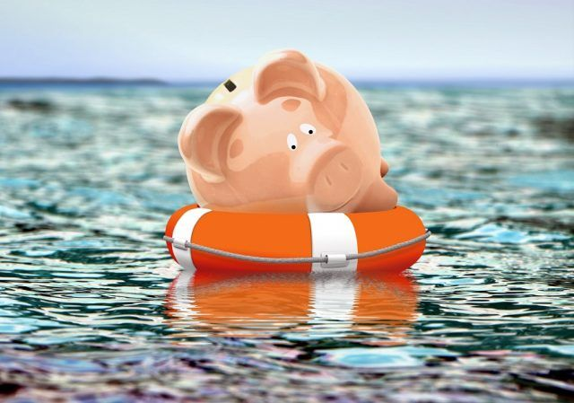Piggy bank floats on buoy on the open ocean