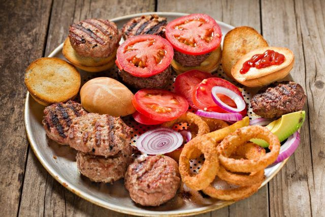 metal tray full of roasted buns, grilled miniature patties, sliced tomatoes