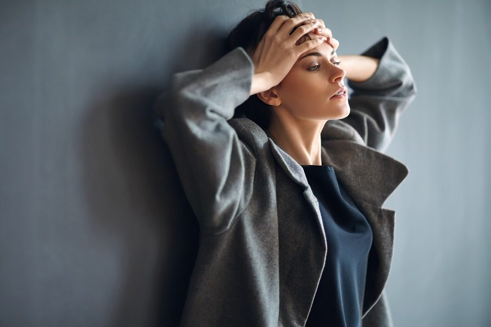 woman in business clothes holding her head and looking very tired