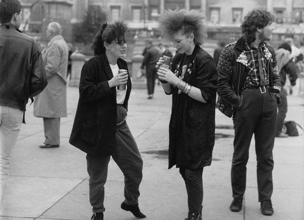 Two young women in post-punk fashions drinking beer from cans