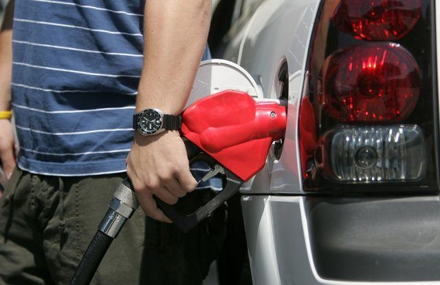 Daniel Sherman pumps gasoline into his car at a Chevron filling station
