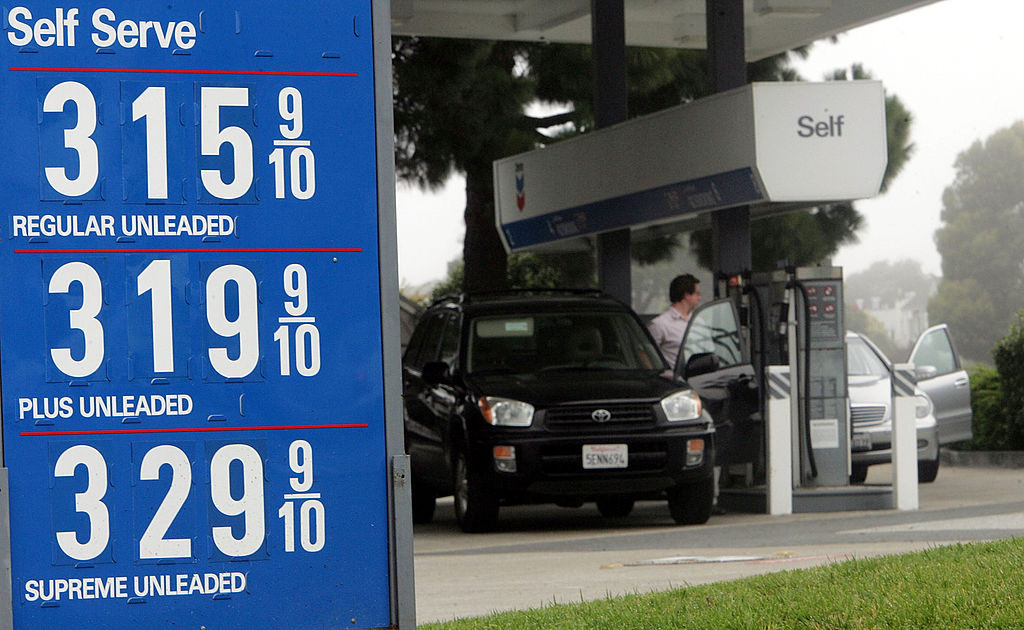 People fill their cars at a Chevron service station