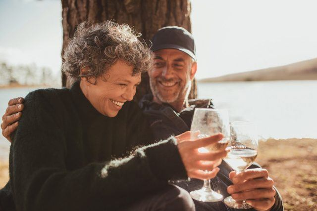 Mature couple having a glass of wine at campsite.