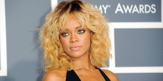 Rihanna stands on a red carpet staring straight ahead while wearing a black dress.