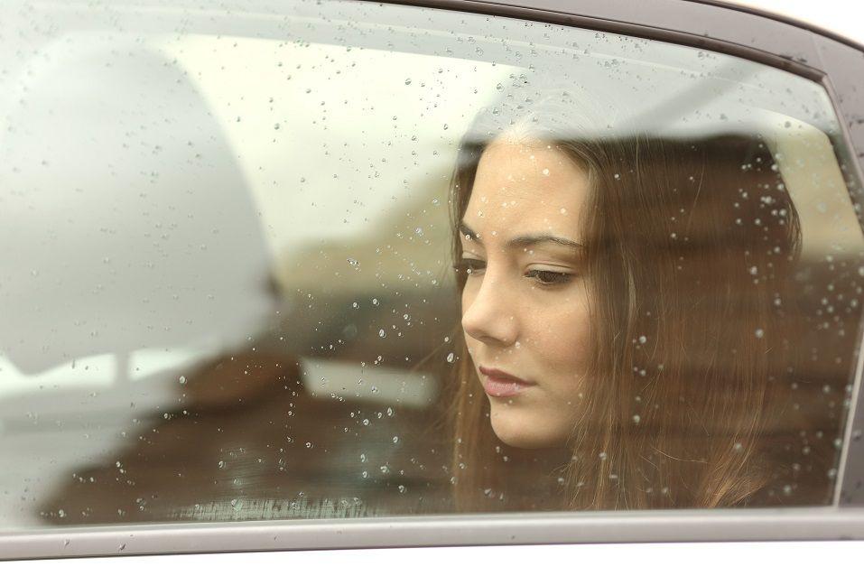 Sad woman looking down through a car window