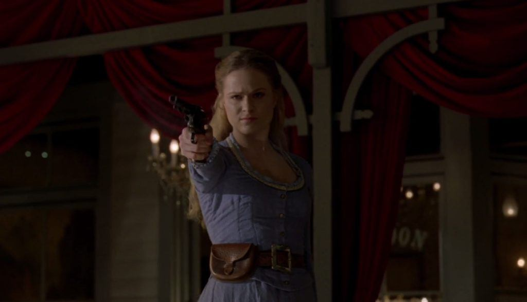 Dolores aiming a gun in front of a western backdrop